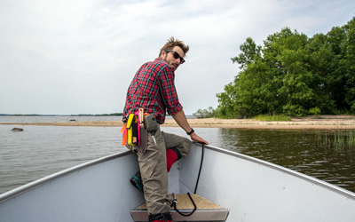 Research Technician Ira navigates among islands at the helm of a boat in the lakes of Ontario (Photo: Scott Nielsen)